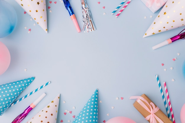 Birthday frame made of balloons; party horn blower; party hat and sprinkles on blue background Free Photo