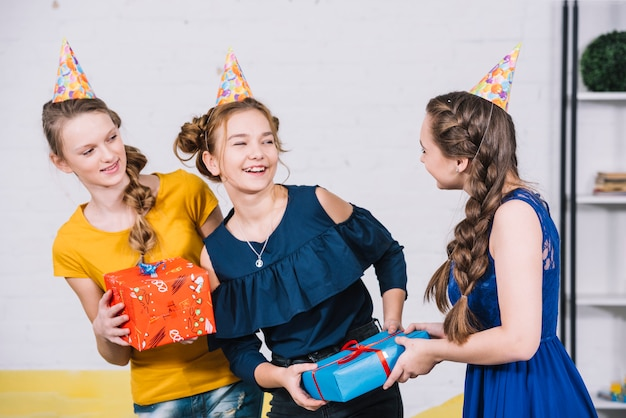 Birthday girl receiving the gift box from her friends at home Free Photo