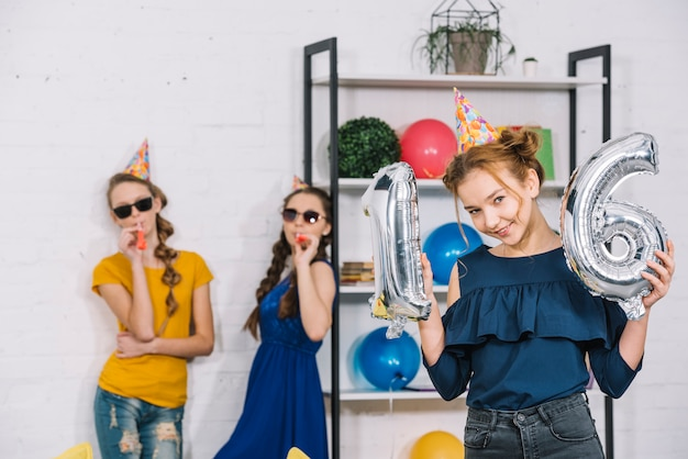 A birthday girl showing numeral 16 foil silver balloons with her two friends blowing party blower Free Photo