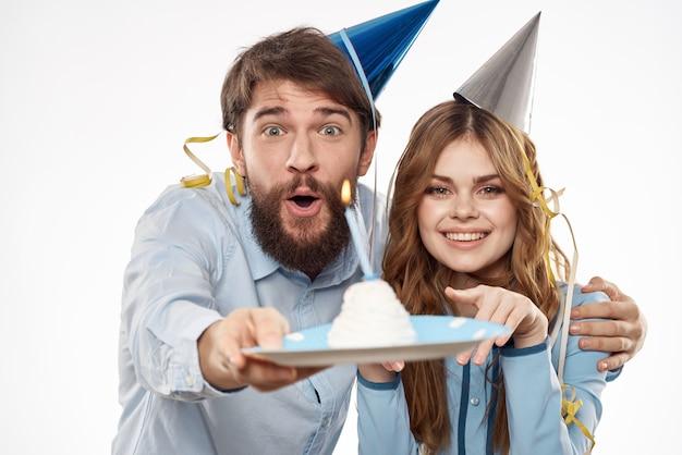 День рождения мужчины и женщины с кексом и свечой в шляпе партии, белый фон Premium Фотографии