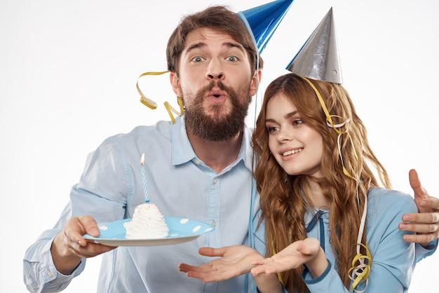 День рождения мужчины и женщины с кексом и свечой в праздничной шапке, белая стена Premium Фотографии