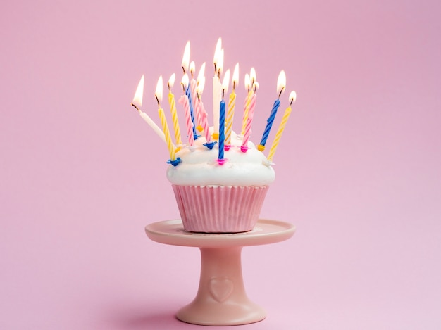 Birthday muffin with colorful candles on pink background Free Photo