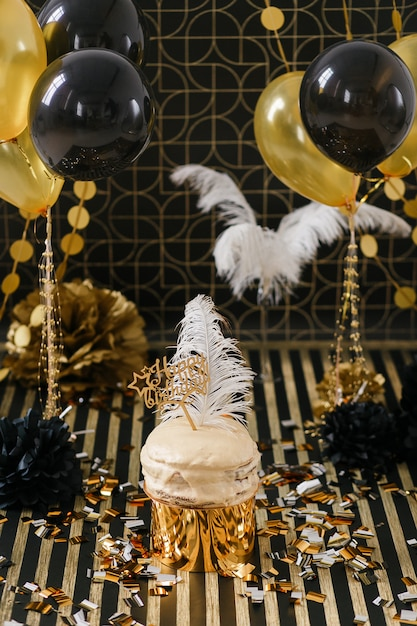 Birthday party cake with golden and black decor various balloons. Free Photo