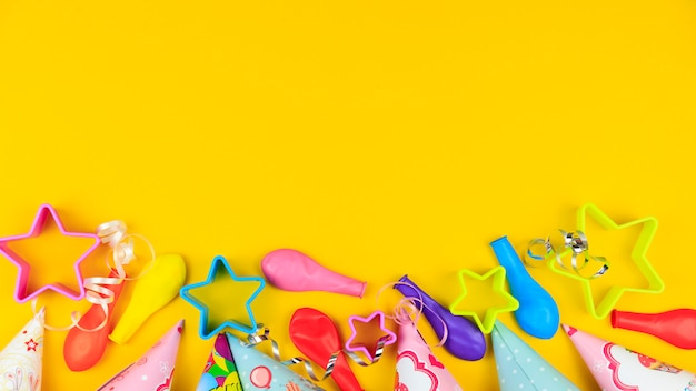 Birthday party caps, balloon and stars on yellow background Premium Photo