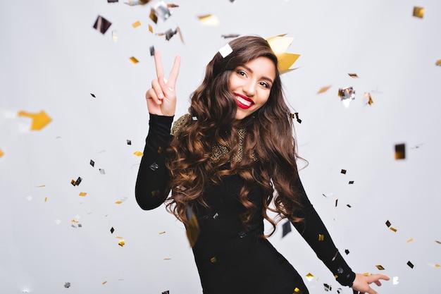 Festa di compleanno, carnevale di capodanno. giovane donna sorridente che celebra un evento luminoso, indossa un abito nero di moda elegante e una corona gialla. coriandoli scintillanti, divertirsi, ballare. Foto Gratuite