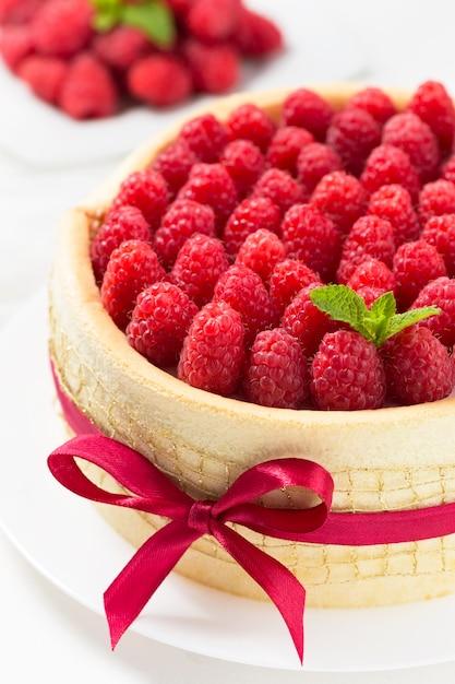 Birthday spongecake with raspberries decorated red ribbon and bow Premium Photo