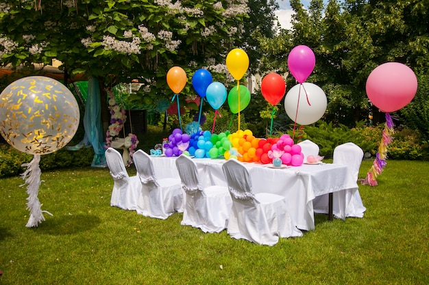 Birthday table with rainbow balloons. summer holiday in the park. Premium Photo