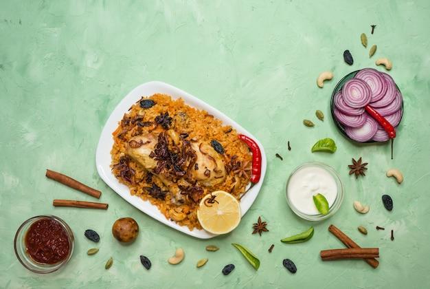 Очень вкусный пряный цыпленок biryani в белом шаре на зеленой предпосылке, индийской или пакистанской еде. Premium Фотографии