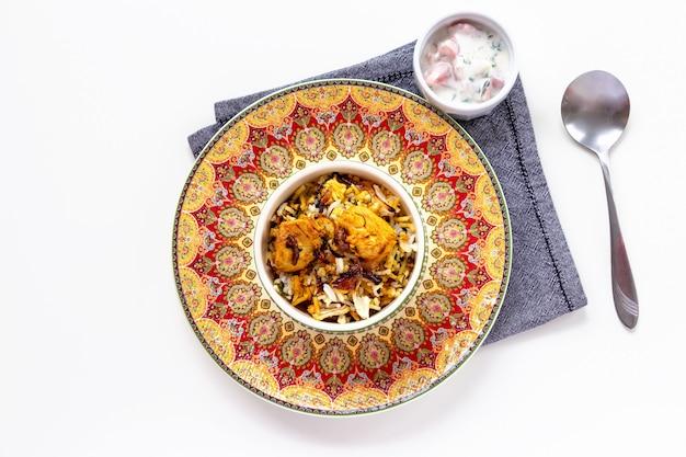 Индийская курица biryani подается с йогуртом помидор раита на белом фоне. выборочный фокус. Premium Фотографии