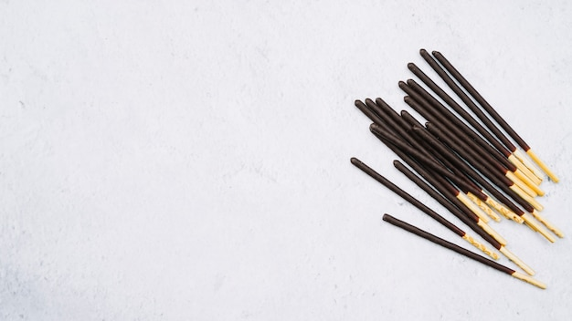 Biscuit sticks in chocolate on white backdrop Free Photo