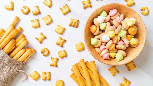 Бисквитные палочки с разноцветным сахарным печеньем в миске Premium Фотографии