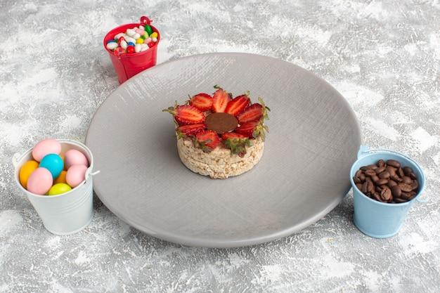イチゴと紫色のプレートの中に丸いチョコレートが入ったビスケット、コーヒーの種子とキャンディー 無料写真