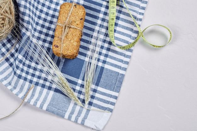 テーブルクロスと白い背景の上のビスケットと巻尺。高品質の写真 無料写真