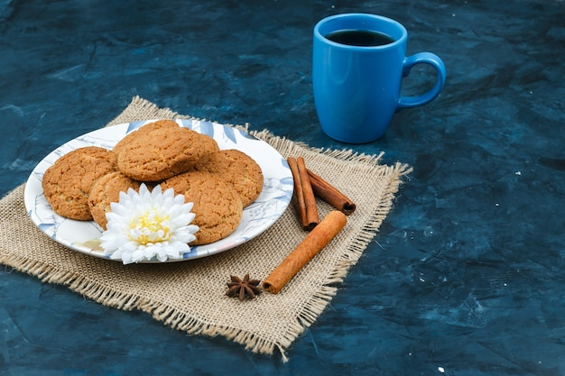 Biscuits and coffee cup on a dark blue background Free Photo