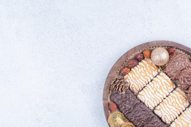 Biscotti, frutta secca e palle di natale su tavola di legno. Foto Gratuite