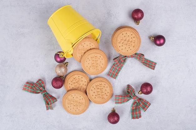 白いテーブルの上のリボンとクリスマスボールで飾られたバケツのビスケット。高品質の写真 無料写真