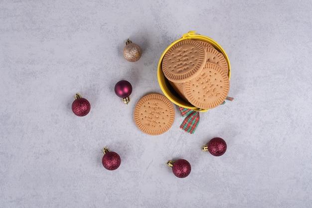 白いテーブルの上のロープとクリスマスボールで飾られたバケツのビスケット。高品質の写真 無料写真