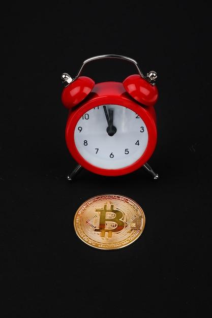 Биткойн и красный будильник на черном фоне. концепция криптовалюты. монета золотого цвета. Premium Фотографии