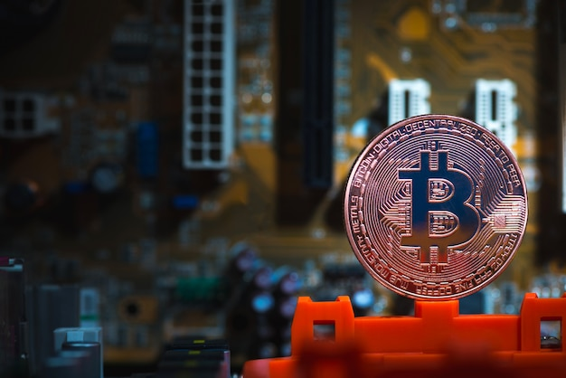 Bitcoin digital currency on motherboard Premium Photo
