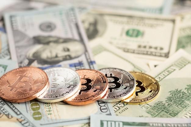 Биткойн в различных цветах поверх долларовых купюр Бесплатные Фотографии