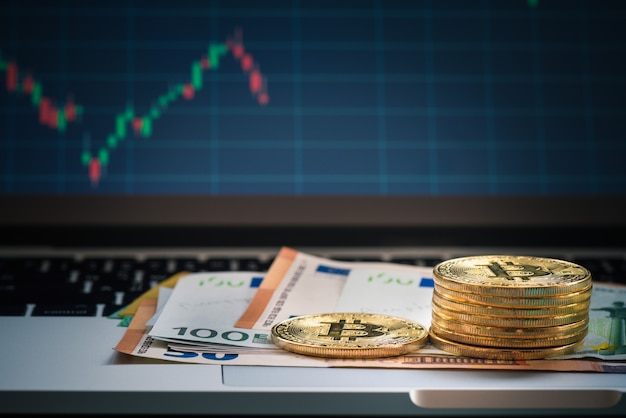 Bitcoin with euro banknote and monitor, uero banknote over keyboard with forex statistic graph Premium Photo