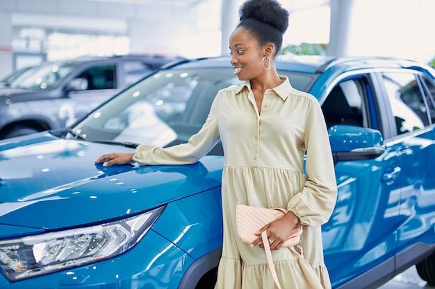 대리점에서 파란 차 옆에 포즈 흑인 아프리카 계 미국인 여자 프리미엄 사진