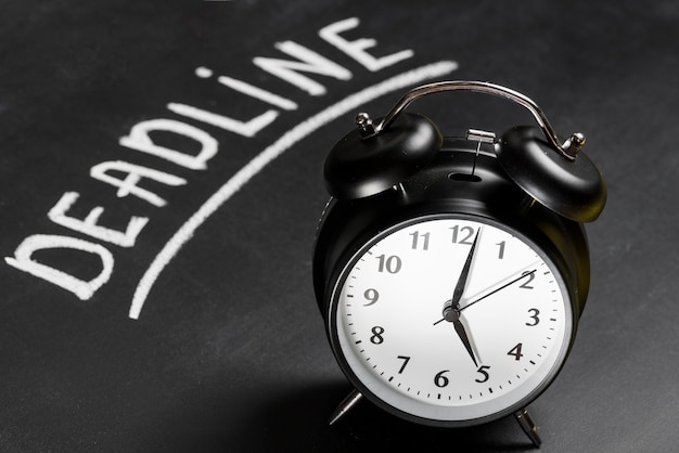 Black alarm clock on chalkboard with deadline word written Free Photo