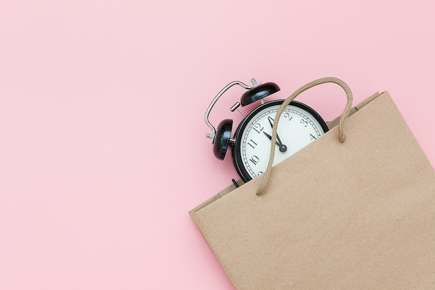 Black alarm clock in craft package on pink Premium Photo