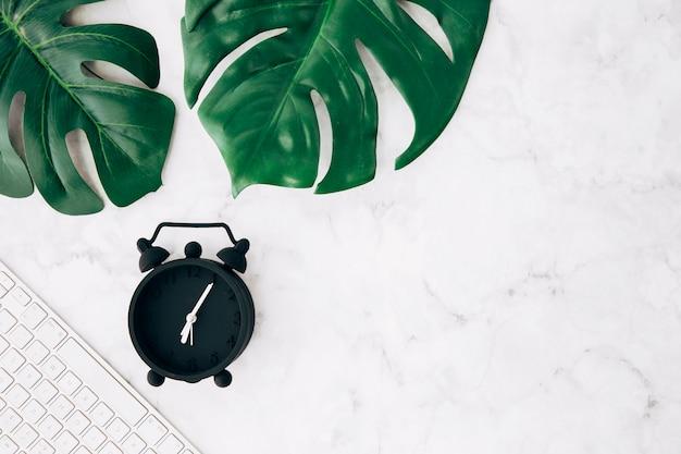 검은 알람 시계; 흰색 대리석 배경에 키보드와 녹색 몬스 테라 잎 무료 사진