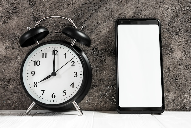 Black alarm clock and smartphone with white blank screen on desk against concrete black wall Free Photo