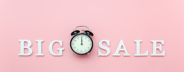 Black alarm clock and text big sale from white volume letters on pink Premium Photo