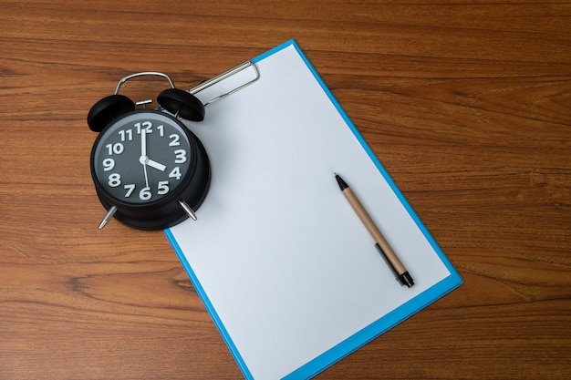 Black alarm clock with clipboard and white paper and pen Premium Photo