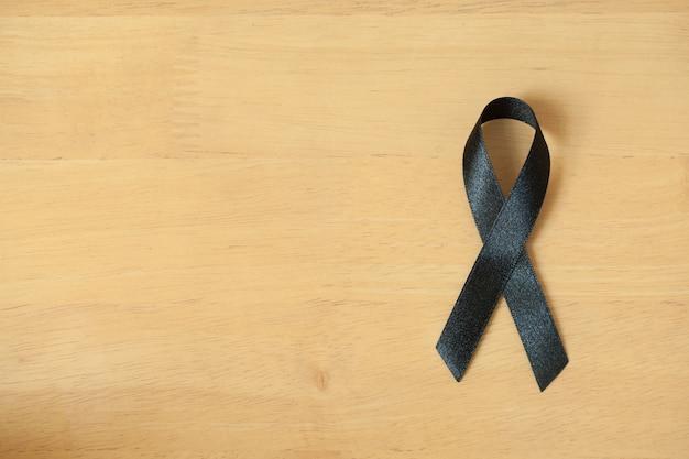 Black Awareness Ribbon On Wooden Background Mourning And Melanoma