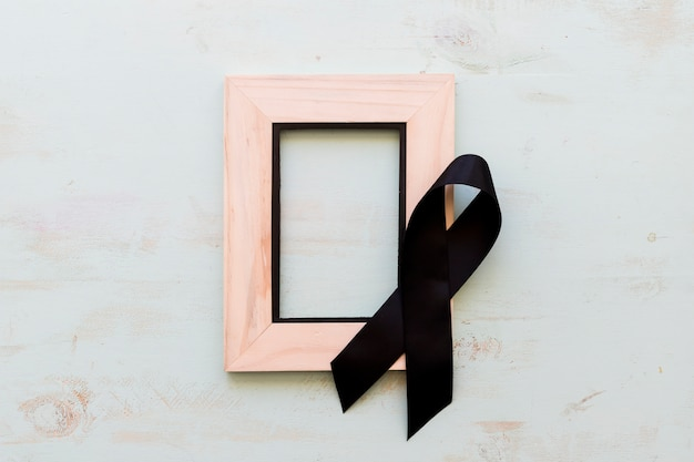Black awareness ribbon on wooden empty frame over the wooden background Free Photo