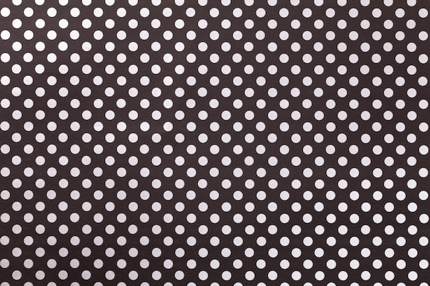 Black background from wrapping paper with a pattern of white polka dot closeup. Premium Photo