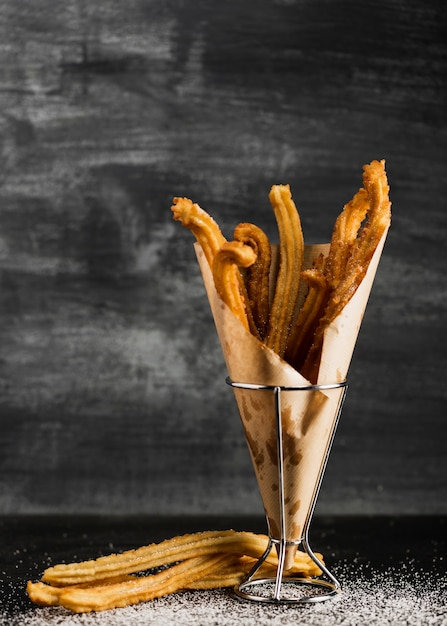 Black background with churros on a wrapping paper Free Photo