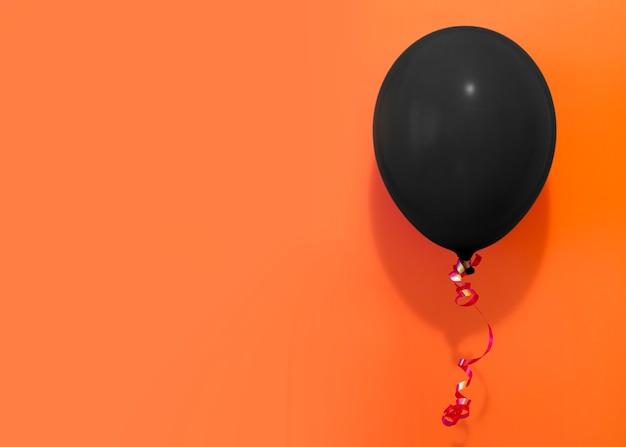 Black balloon on orange background Free Photo