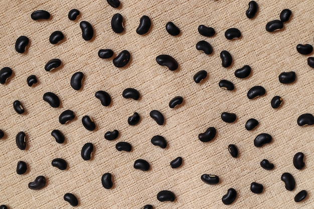 Black beans seeds on cream fabric Premium Photo
