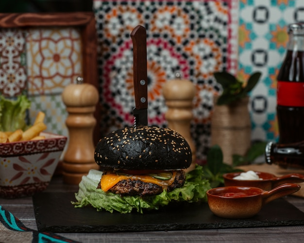 A black beef burger stuffed with vegetables and apetizers and served with cheddar cheese Free Photo