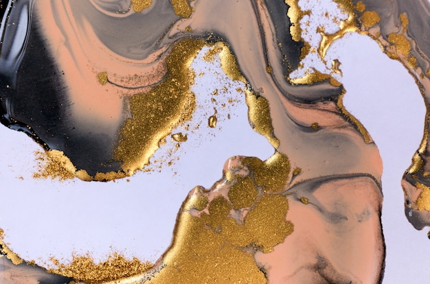 Black, beige and gold mixed inks splattered on white paper background. Premium Photo
