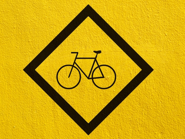 A black bicycle points painted on a stucco wall outside Premium Photo