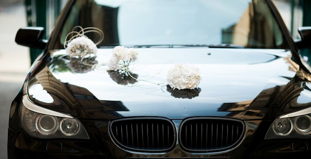 Black bmw decorated with white wedding bouquets Free Photo