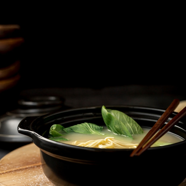 Black bowl with noodle soup on a black background Free Photo