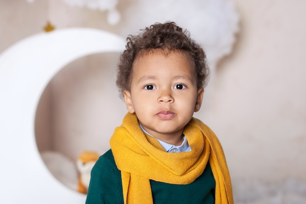 Black boy close up. portrait of a cheerful smiling black boy in a yellow scarf. portrait of a little african american. black guy. pensive child. childhood. child plays in kindergarten. little boy face Premium Photo