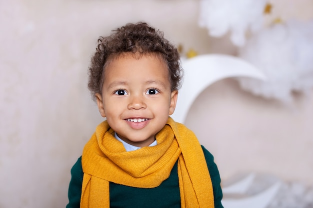 Black boy close up. portrait of a cheerful smiling black boy in a yellow scarf. portrait of a little african american. black guy. pensive child. childhood. child plays in kindergarten. little boy face Premium Photo