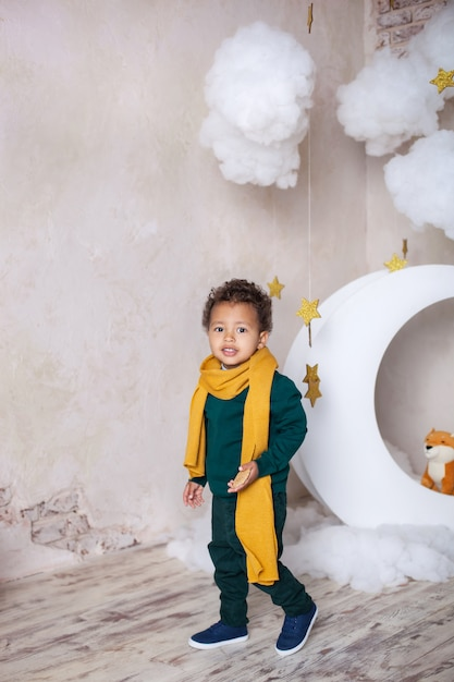 A black boy stands near month, luna, among stars. a child in game, in fantasy. adventures of little prince. african american boy. childhood. child plays in kindergarten. child preschool education. Premium Photo