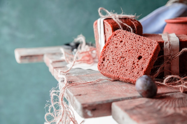 Black bread slices wrapped with white paper and plums on a wooden table. Free Photo