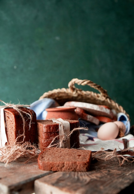 Black bread slices wrapped with white paper and rustic thread with a pot of milk, eggs and garlic on a white towel inside a basket. Free Photo