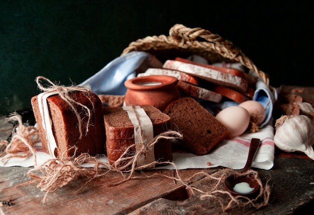 Black bread slices wrapped with white paper and tustic thread with a pot of milk, eggs and garlic on a white towel. Free Photo
