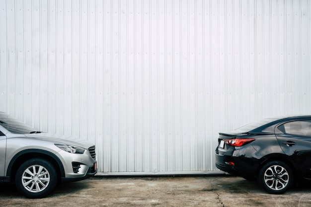 Black and bronze color cars parking on concrete floor with metal sheet wall Premium Photo